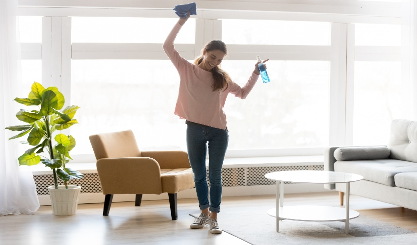 Happy woman dancing during spring cleaning.