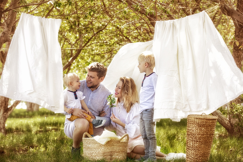 Loving family enjoying the summer sun together while hanging laundry on the clothesline.