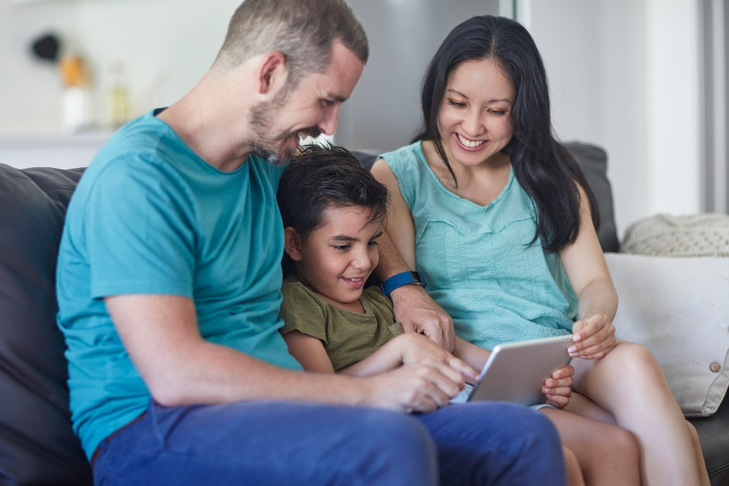 Happy family smiling, laughing, and having fun while playing games together on a tablet.