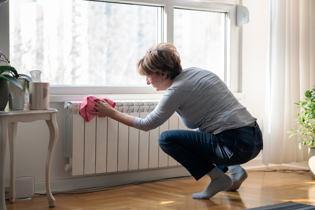 Woman performing routine cleaning on a heating unit, one of a few simple but important winter furnace maintenance tips.