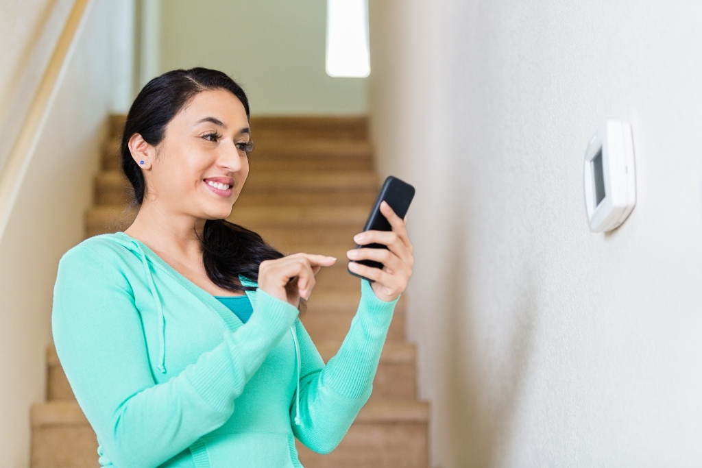 Woman setting her programmable thermostat - a great investment for extending the lifespan of HVAC equipment.